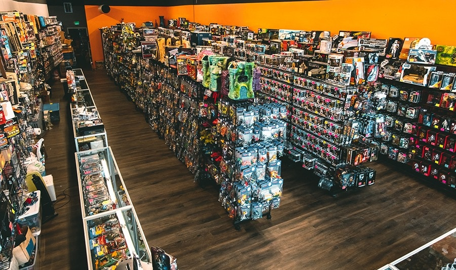 Store floor with several rows of shelves with popular collectible merchandise within the comic book community